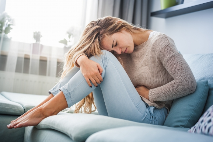 Young woman suffering from strong abdominal pain while sitting on sofa at home; blog: Painful Periods: When to See Your Gynecologist